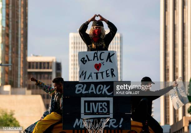 TOPSHOT Protesters ride on a school bus during a demonstration over the death of George Floyd while in Minneapolis Police custody in downtown Los...