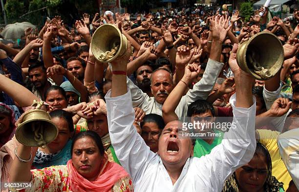 Protesters ring bell and shout slogans during protest demonstration as city witnessed a near total bandh in protest against alleged desecration of a...