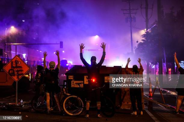 TOPSHOT Protesters rise their hands up during a demonstration in Minneapolis Minnesota on May 29 over the death of George Floyd a black man who died...