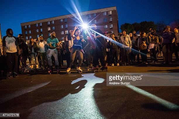 Protesters roller skate in front of riot police before a mandatory, city-wide curfew of 10 p.m. Near the CVS pharmacy that was set on fire yesterday...
