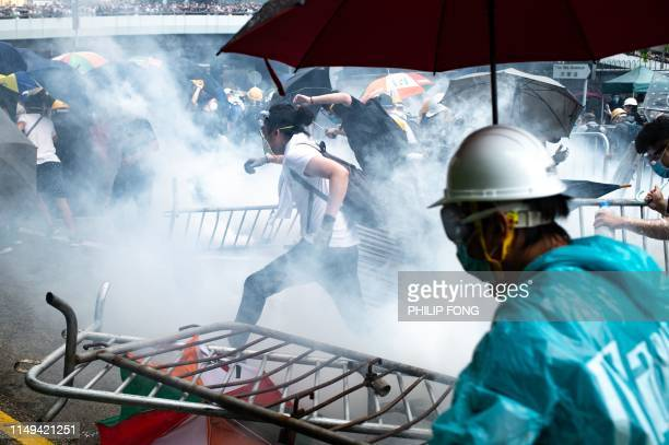 TOPSHOT Protesters run after police fired tear gas during a rally against a controversial extradition law proposal outside the government...