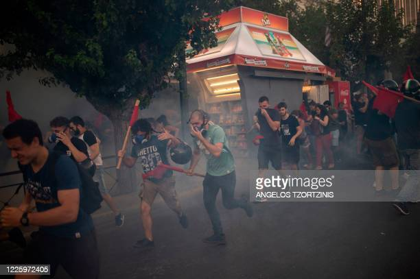 Protesters run amid teargas smoke as they clash with riot police during a demonstration outside the parliament to protests against the upcoming law...