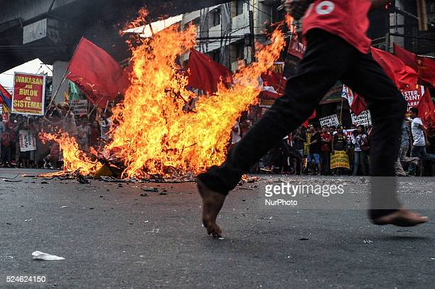 Protesters run around the burnt effigy shouting their protests at the historic Mendiola Bridge in San Miguel Manila on Saturday 30 November 2013...
