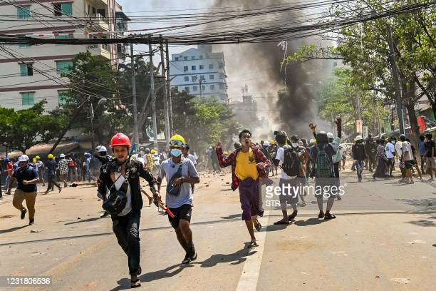 Protesters run as tear gas is fired during a crackdown by security forces on a demonstration against the military coup in Yangon's Thaketa township...