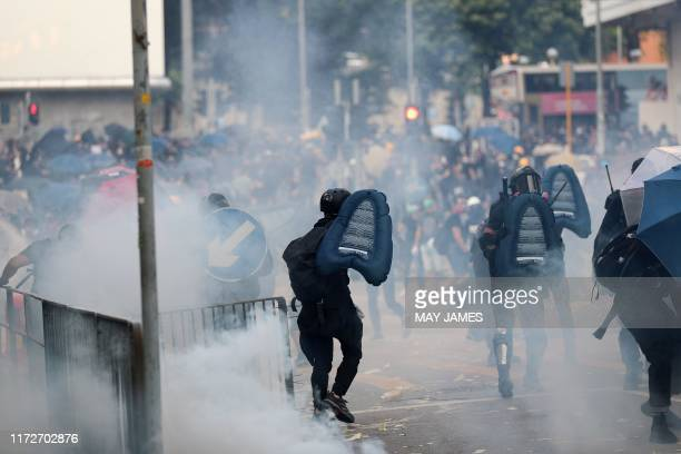 Protesters run away after police fired tear gas during a demonstration in the Sham Shui Po area in Hong Kong on October 1 as the city observes the...