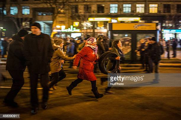 Protesters run away from police carrying tires in order to light fires during a rally on Maidan Square in Kiev on November 21 on the third...