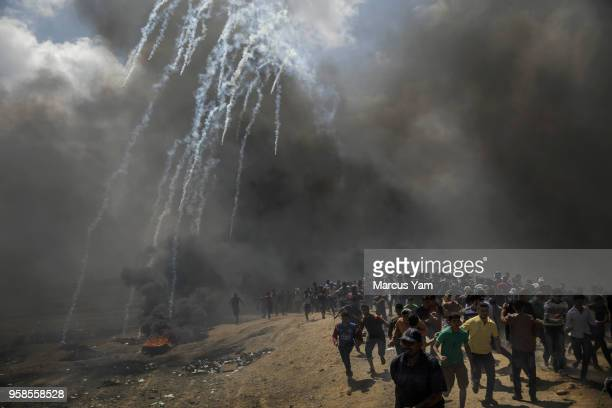 Protesters run away from tear gas dispersed by Israeli forces as they inch closer to the border fence separating Israel and Gaza on May 14 2018 in a...