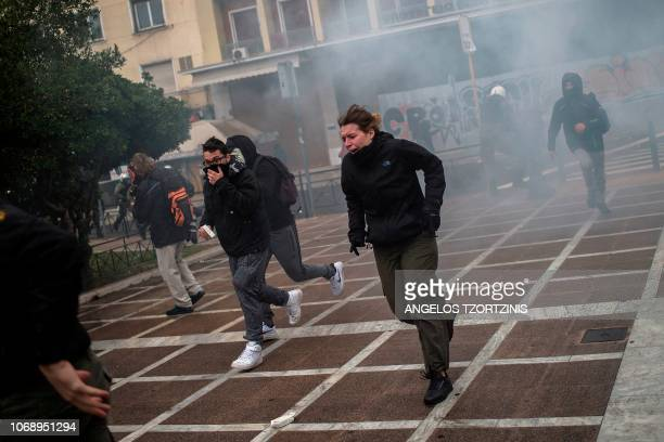 Protesters run away from tear gas during a demonstration in Athens on December 6 2018 to commemorate the 10th anniversary of fatal shooting of a...