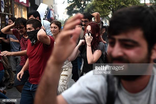 Protesters run away from tear gas during a demonstration on July 24, 2015 in Istanbul, after the explosion in the town of Suruc four days earlier....