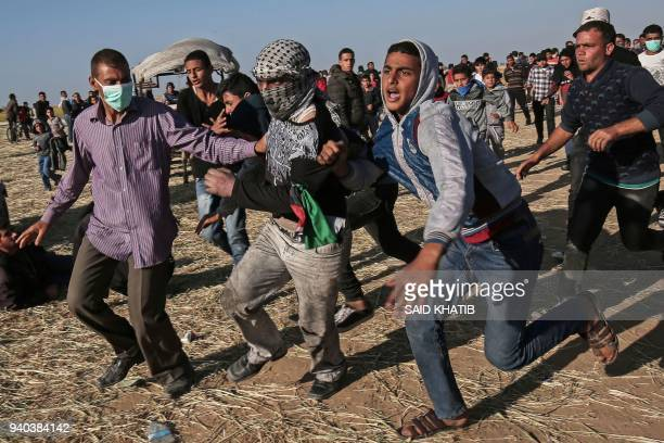 TOPSHOT Protesters run during clashes with Israeli security forces following a demonstration near the border with Israel east of Khan Yunis in the...