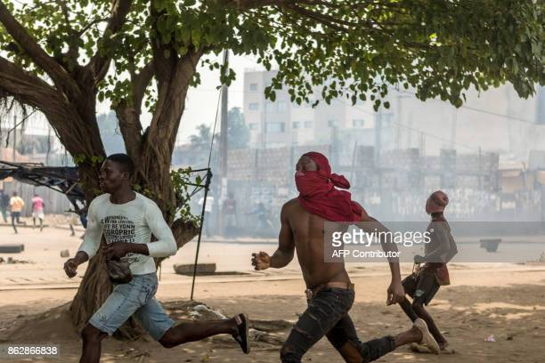 Protesters run during clashes with security forces during an anti-government protest in Lome on October 18, 2017. Protesters erected makeshift...