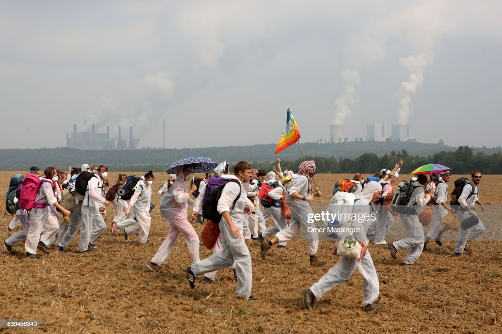 Protesters run during their protest against open-pit coal mines in the Rhineland (Rhenisch) region of mines west of Cologne on August 26, 2017 near Bedburg, Germany. Thousands of protesters seeking to bring attention to the impact of coal on climate change have converged on the region for two days of disruptive disobedience. The mines, which include the Hambach, Garzweiler, Inden and Bergheim mines, are operated by German utility RWE and produce lignite coal.