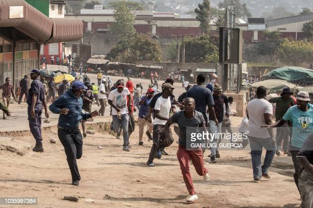 Protesters run for cover as they clash with eSwatini anti-riot police on September 19, 2018 in Manzini. - Undercurrents of dissent have surfaced this...