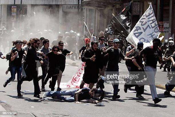 Protesters run from riot police during May Day protests on May 1 2010 in Athens Greece Thousands of protesters gathered in Athens and other Greek...