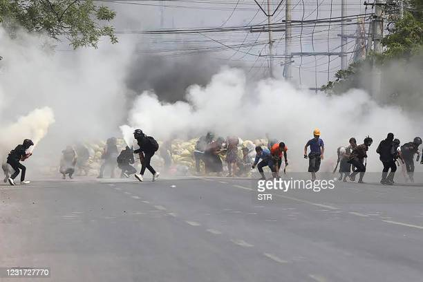 Protesters run from tear gas fired by security forces, as some demonstrators also let off fire extinguishers, next to a barricade set up during the...
