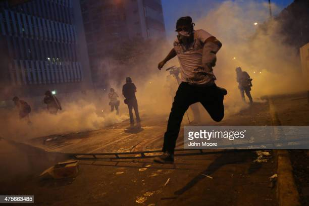 Protesters run from tear gas fired by the Venezuelan national guard during an antigovernment demonstration on February 27 2014 in Caracas Venezuela...