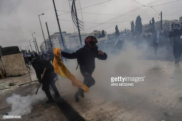 Protesters run from tear gas in Athens on January 20 2019 during a demonstration against the agreement with Skopje to rename neighbouring country...