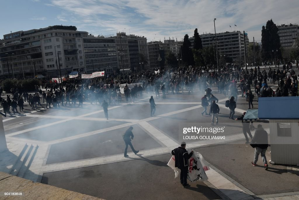 Protesters run from tear gas in front of the Greek parliament in Athens, on January 12, 2018, during a demonstration against changes to a 36-year-old industrial action law demanded by the country's creditors. /