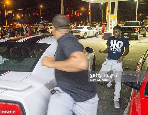 Protesters run through a gas station parking lot as law enforcement in riot gear charge the protesters to make arrests on July 10 2016 in Baton Rouge...