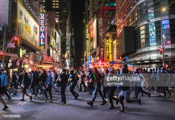 Protesters rush past Times Square after an 11pm curfew during a night of marches and vandalism over the death of George Floyd on June 1, 2020 in New...