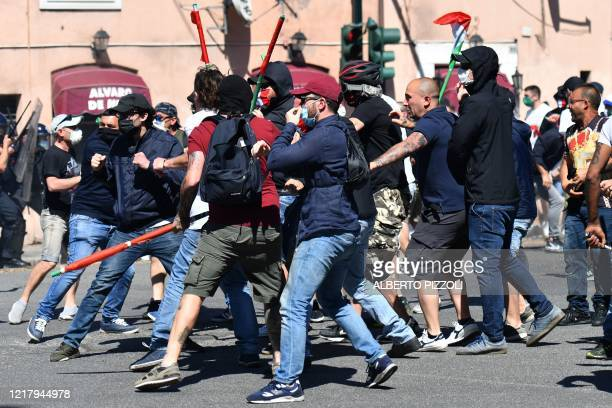 Protesters scuffle during clashes between anti-riot police and neo-fascist groups, extremists and ultras from Italy's football clubs demonstrating...