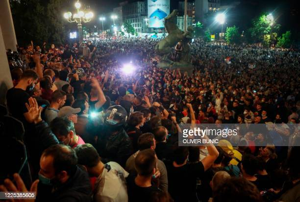 Protesters scuffle with police in front of the National Assembly building in Belgrade, on July 7 as Serbian police fired tear gas to disperse...