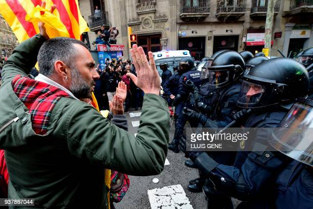 Protesters scuffle with riot police blocking the road leading to the central government offices at a demonstration in Barcelona on March 25, 2018...
