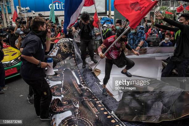 Protesters seen destroying a mock-up tank during the car mob rally. Anti-government protesters gathered at Asok intersection before they drove their...