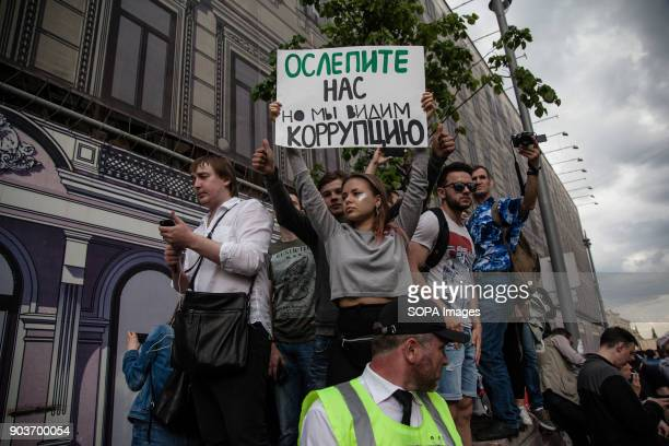 Protesters seen displaying placards during the demonstration Anticorruption protest organised by opposition leader Alexei Navalny at Tverskaya Street