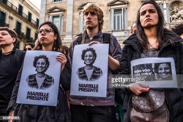 Protesters seen displaying posters with the portrait of Marielle Franco Hundreds of people gathered in Barcelona in memory of the Brazilian activist...