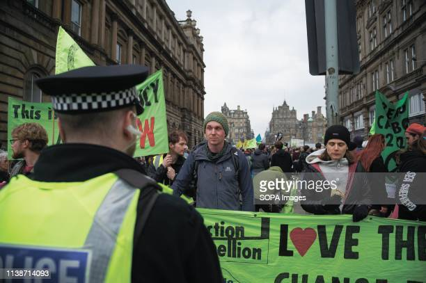 Protesters seen holding a banner in front of a policeman during the demonstration Extinction Rebellion held a lockdown of Edinburgh's North Bridge as...