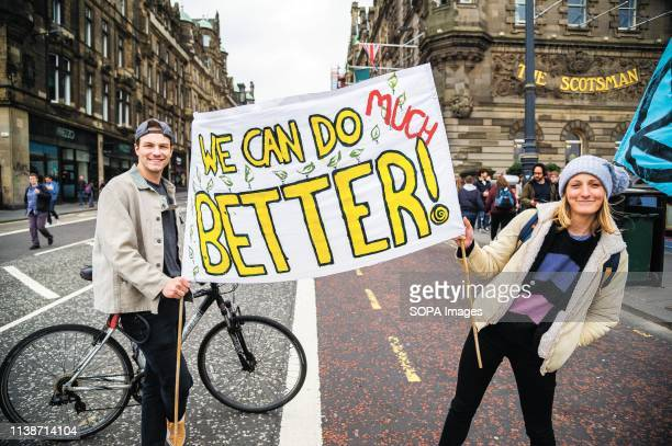 Protesters seen holding a banner in the middle of the road during the demonstration Extinction Rebellion held a lockdown of Edinburgh's North Bridge...