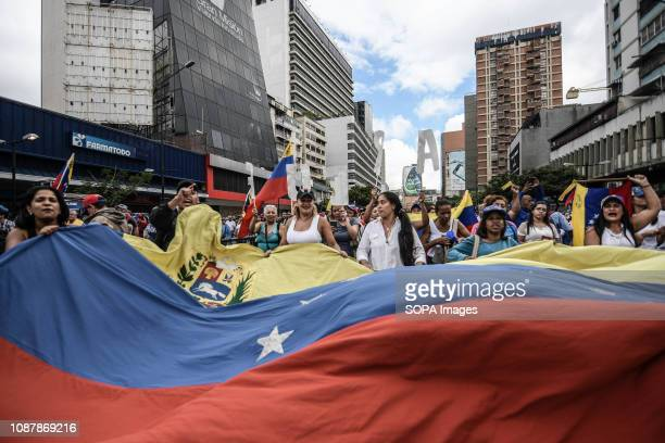 Protesters seen holding a huge Venezuela flag during a demonstration against Nicolas Maduro policies Rally against the government of Venezuelan...