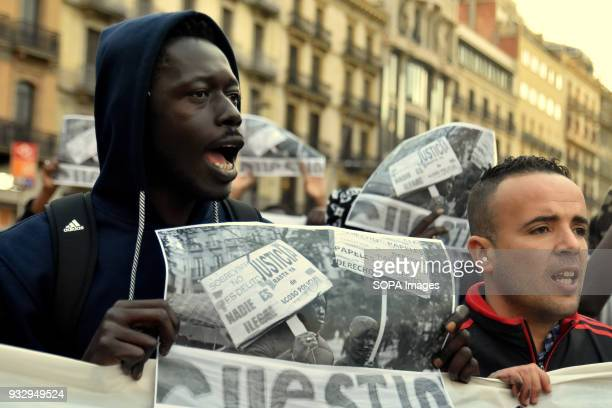 Protesters seen holding placards during a demonstration in memory of Mame Mbaye Mame Mbaye a Senegalese street vendor who died in Madrid from cardiac...