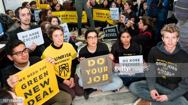 Protesters seen holding placards during the Sunrise Movement protest inside the office of US Representative Nancy Pelosi to advocate that Democrats...