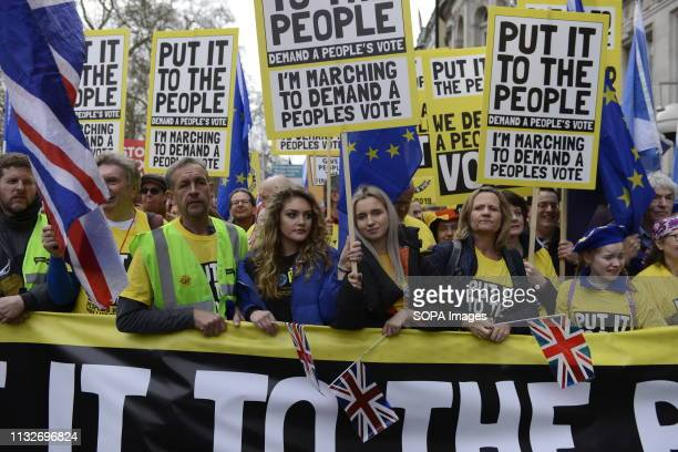 Protesters seen holding several placards and a banner during the demonstration Over a million people marched peacefully in central London in favor of...