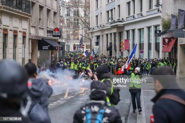 Protesters seen in tear gas smoke in Champ Elysees near Arc De Triomphe during the Yellow Vest demonstration Clashes and vandalism which have...