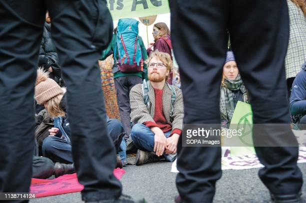 Protesters seen seating down in the middle of the road during the demonstration Extinction Rebellion held a lockdown of Edinburgh's North Bridge as...