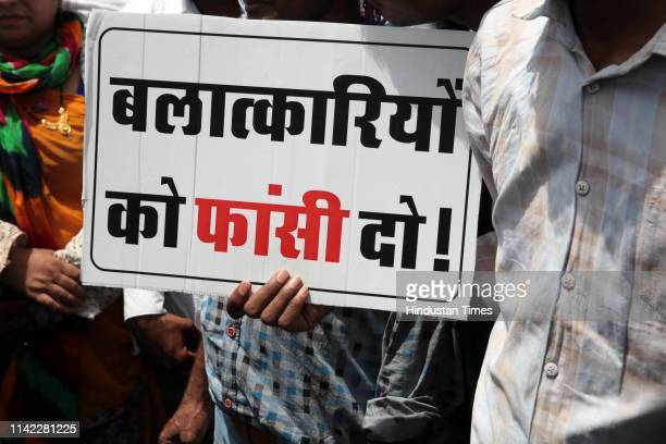 Protesters seen with placards during a protest march to demand capital punishment for Alwar gang-rape accused, near Chief Minister's residence on May...
