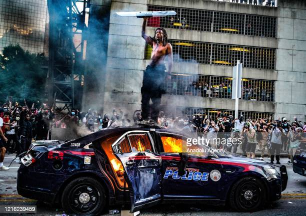 Protesters set a police vehicle on fire during a protest following the death of George Floyd outside of the CNN Center next to Centennial Olympic...