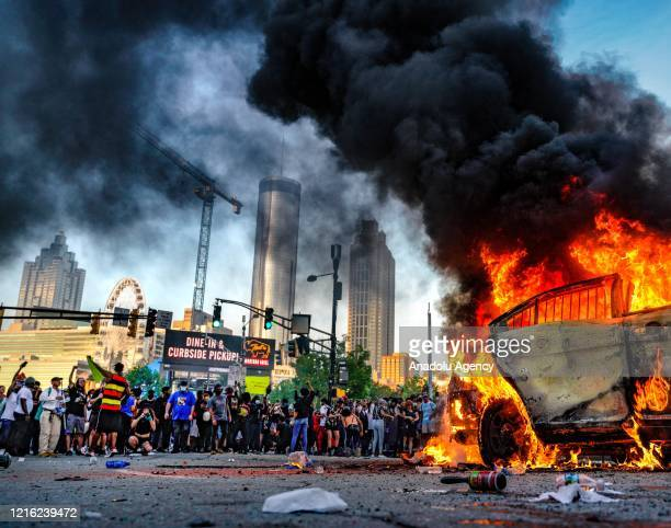 Protesters set a vehicle on fire during a protest following the death of George Floyd outside of the CNN Center next to Centennial Olympic Park in...