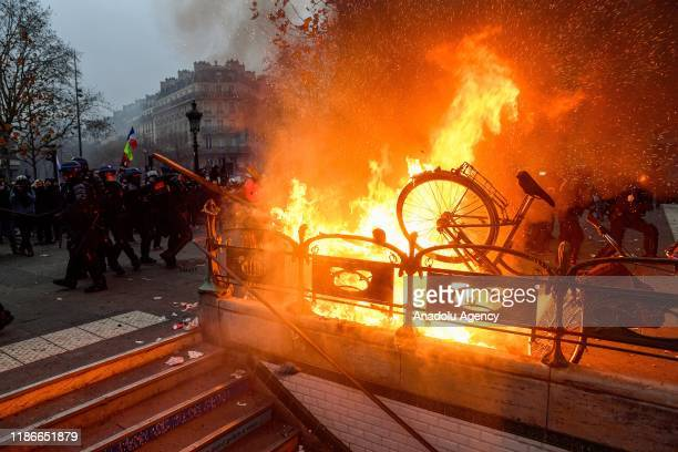 Protesters set fire on the entrance of a subway during a protest against President Emmanuel Macron's controversial pension plans and in support of...