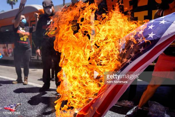 Protesters set fire to an American flag near President Donald Trumps Star on the Hollywood Walk of Fame part of the Demonstrate How to Dishonor the...