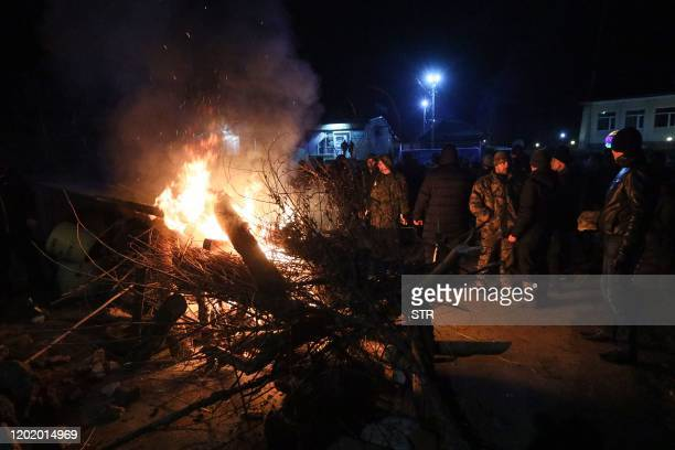 Protesters set fire to barricades as they block a road ahead of the arrival of evacuees from coronavirus-hit China for quarantine at a medical...