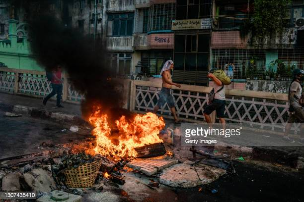 Protesters set fire to tires near a barricade to try and prevent the advance of military junta forces on March 16, 2021 in Yangon, Myanmar. Myanmar's...