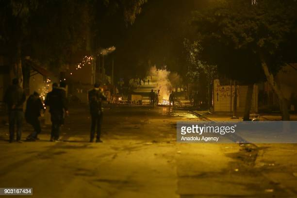 Protesters set tires an garbage containers on fire to block a road during a demonstration against price hikes at al-Tadamun neighborhood of Tunis,...
