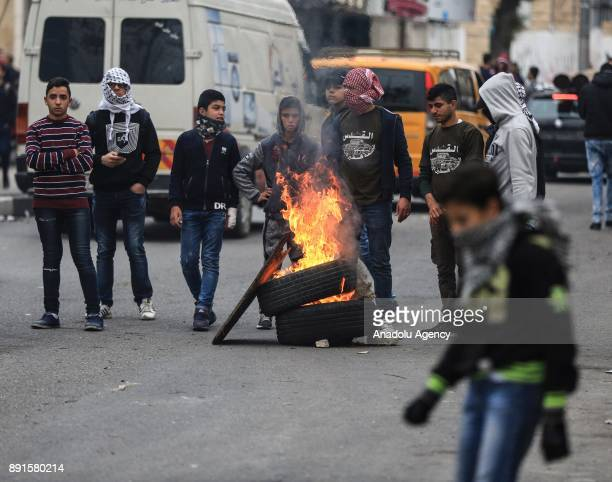 Protesters set tyres to fire during a protest against US President Donald Trumps announcement to recognize Jerusalem as the capital of Israel and...