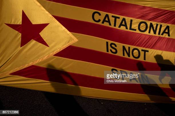 Protesters shadows are seen on a Catalan flag as thousands of citizens gather in Plaza Universitat during a regional general strike to protest...