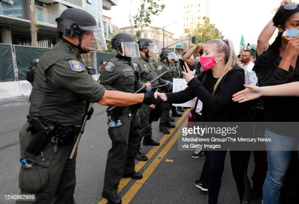 Protesters shake hands with a Santa Clara County Sheriffs officer during a protest of the killing of George Floyd outside of San Jose City Hall in...