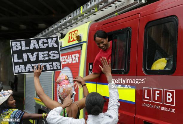 Protesters shake hands with a women in a London Fire Brigade engine as people march in Brixton south London to protest against police brutality in...